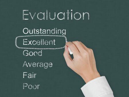 evaluating: la mano maestra evaluar excelente en la pizarra Foto de archivo