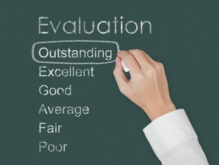 outstanding: teacher hand evaluate outstanding on chalkboard