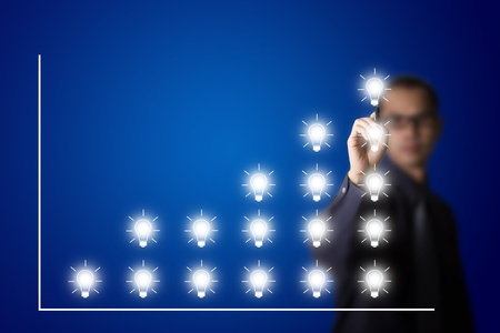 business man drawing increasing idea graph with light bulb symbol photo