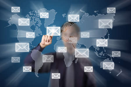 businessman sending mail by push touch screen button on world map background photo