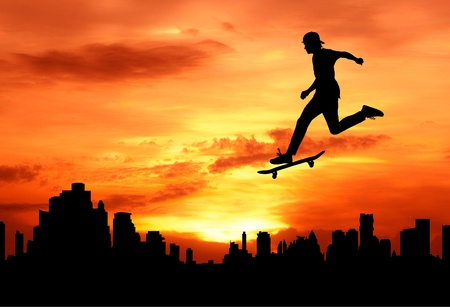young man skateboarder jumping over the city during sunset silhouetted Stock Photo