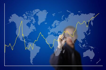 business man drawing fluctuate upward trend graph on world map photo