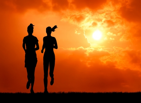 two healthy woman run together at sunrise silhouetted