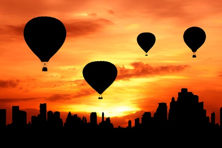 hot air balloons: group of hot air balloon fly over city at sunset silhouetted Stock Photo