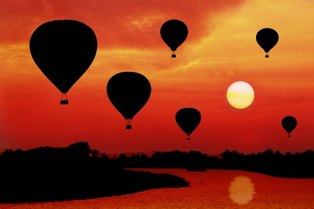 silhouetted hot air balloon racing during sunset photo