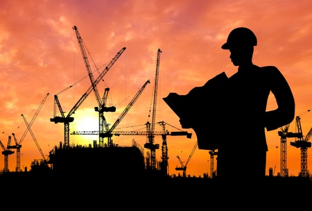 construction project: silhouette of an engineer working on construction site at sunset