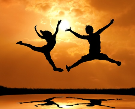 teen silhouette: silhouette of man and woman jumping and touch the sun Stock Photo