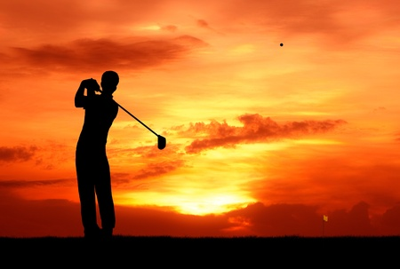 male golfer hit golf ball toward the hole at sunset silhouetted