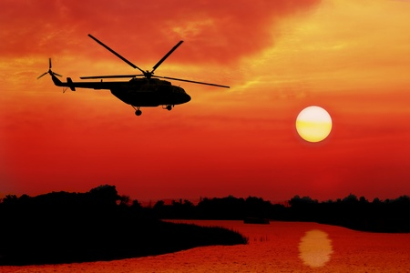 helicopter: silhouette of helicopter fly over land and river during sunrise