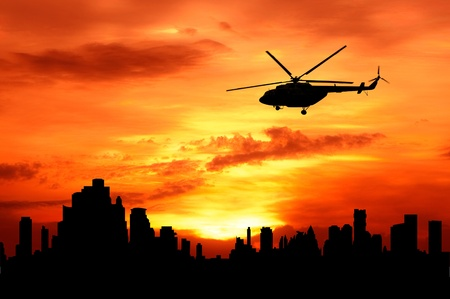 silhouette of helicopter fly over urban building photo
