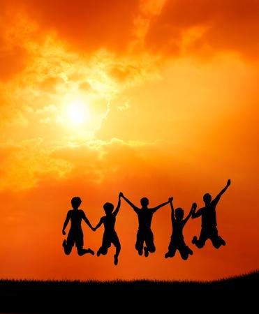 amistad: grupo de amigos adolescentes la libertad de saltar de alegr�a ante la salida del sol silueta Foto de archivo