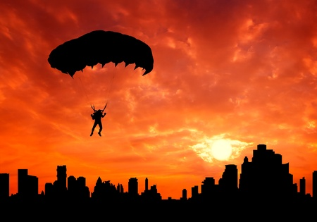 parachute man at sunset silhouetted photo