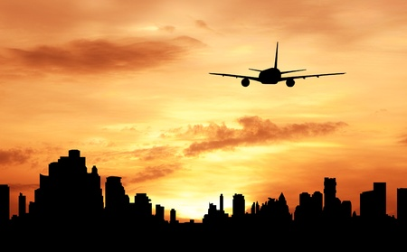 buliding: silhouette of commercial plane fly over city during sunrise Stock Photo
