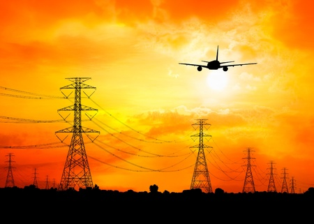atmosphere construction: commercial plane flying over electric pylon at sunset silhouetted