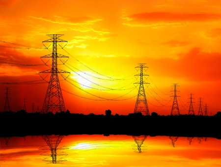 silhouetted electric pylon with power line at sunset photo