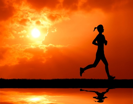 healthy woman running past the sun at sunset silhouetted photo