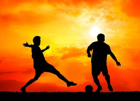 silhouetted: two man soccer player playing with ball during sunset silhouetted