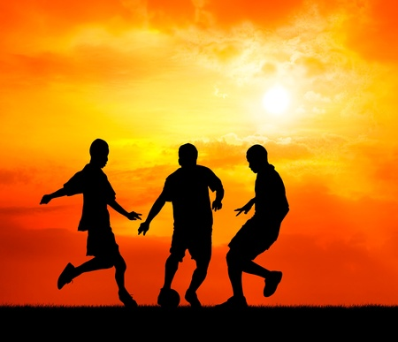 snatch: three man soccer player playing with ball during sunset silhouetted Stock Photo