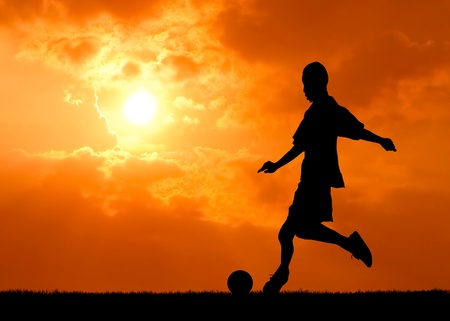 soccer background: soccer player shooting the ball at sunset silhouetted Stock Photo