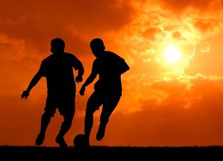 arracher: deux joueurs de football homme jouant avec le ballon au coucher du soleil Banque d'images