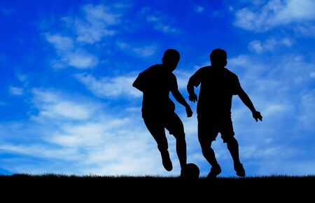 two man soccer player playing with ball at day time silhouetted photo