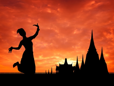 thai dance perform by young woman silhouetted with  temple in thailand background photo