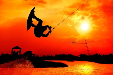 wakeboarding action man surf and jump to  beautiful sky silhouetted , extreme sport photo