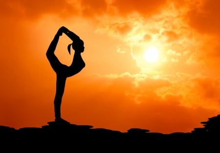 yoga: beautiful woman practise yoga at sunset silhouetted