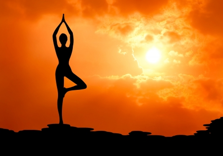 beautiful woman practice yoga at sunset silhouetted Stock Photo - 13224494