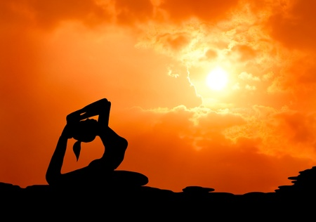 healthy woman practice yoga at sunset silhouetted Stock Photo - 13224482