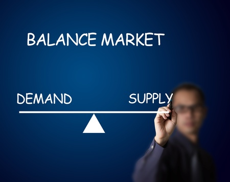 point of demand: businessman drawing balance of demand and supply market on lever Stock Photo