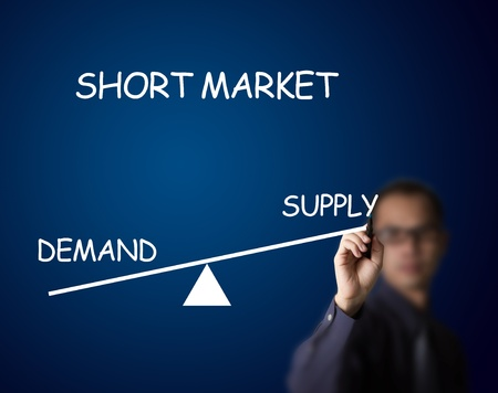 levers: businessman drawing short balance of demand and supply market on lever Stock Photo