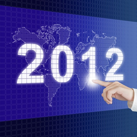 hand pointinng new year 2012 with world map on digital board photo
