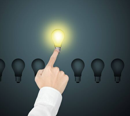 special individual: outstanding bright light bulb symbol of leading idea being pointed by male hand
