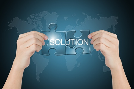 hand holding solution connected jigsaw puzzle with world map background photo