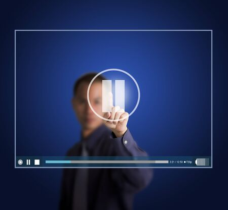 suspend: business man push pause button on touch screen to suspend video clip Stock Photo