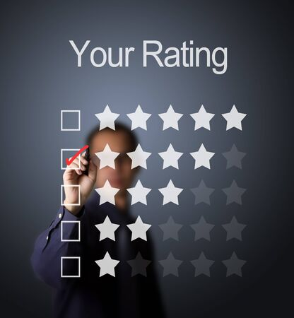 business man writing red mark on four star choice on rating survey form photo