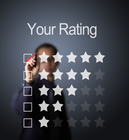 business man writing red mark on five star choice on rating survey form photo