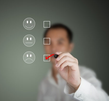 satisfaction client: homme d'affaires de marquage � l'humeur malheureuse sur le formulaire enqu�te de satisfaction clients
