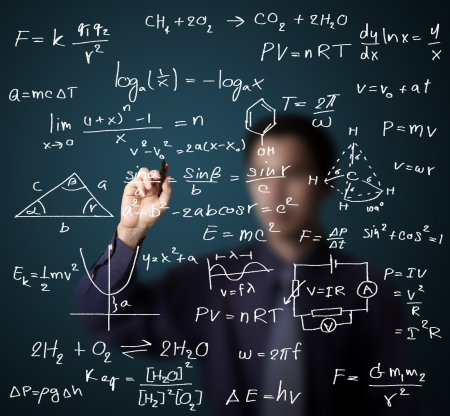 scientific: male teacher writing various high school maths and science formula on whiteboard
