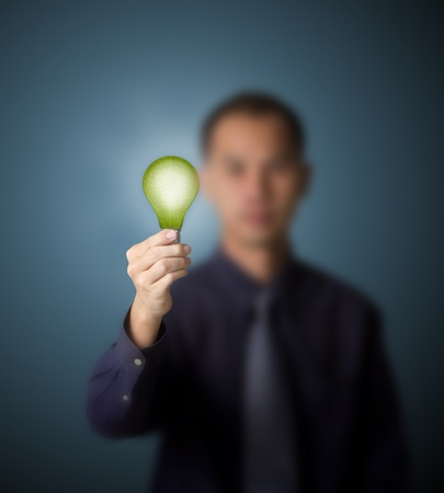 bright future: business man holding  green light bulb, eco concept of new alternative energy
