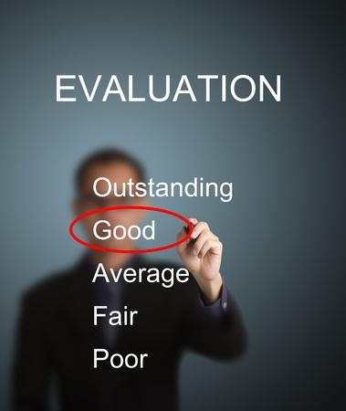 evaluacion: hombre de negocios escribir marca roja en la buena elección en el formulario de evaluación de la encuesta Foto de archivo
