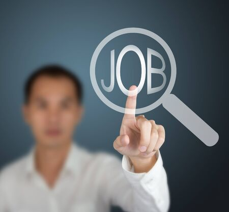 a man pushing touchscreen search button on internet to find the job photo