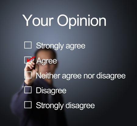 agree: business man writing red mark on agree choice on opinion survey form