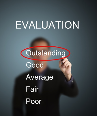 business man write red mark at outstanding choice on evaluation survey form photo