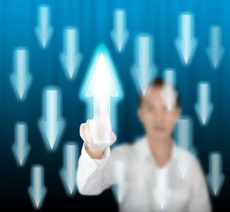 deviate: business man pointing rising arrow against others falling on modern digital screen