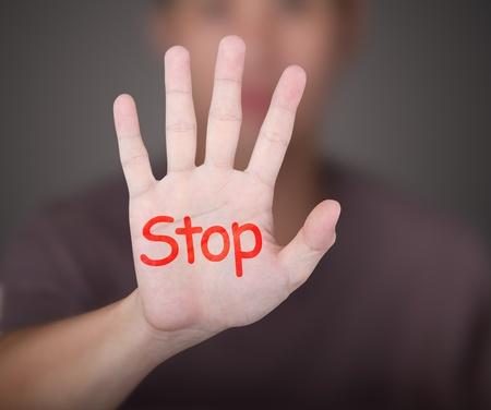 cease: un uomo che mostra la sua mano con arresto parola rosso Archivio Fotografico