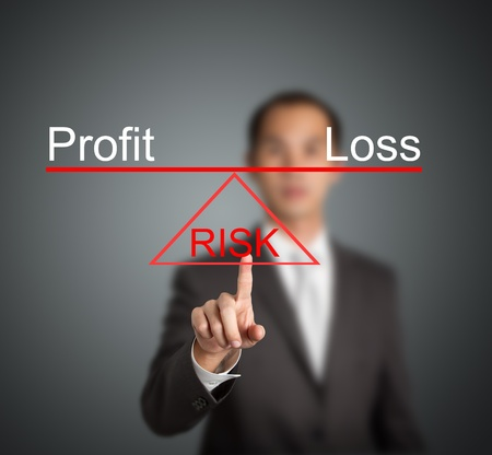 profits: business man showing profit or loss is on balance on sharp point of risk base