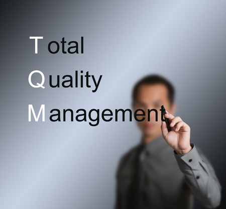 business man writing total quality management  TQM  concept for industry photo