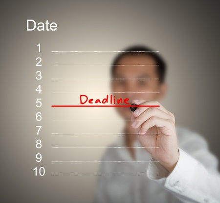 businessman writing word deadline and red line on calendar photo